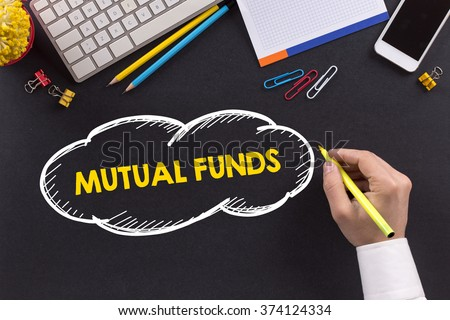 Man working on desk and writing MUTUAL FUNDS - stock photo