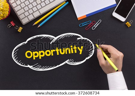 Man working on desk and writing Opportunity - stock photo