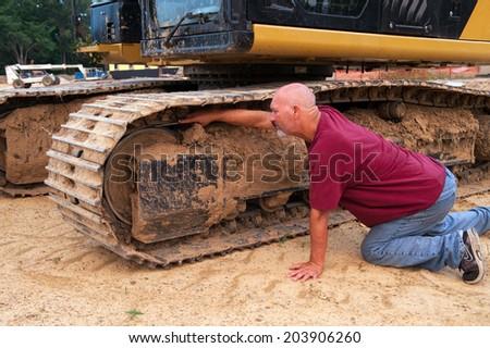 Man working on excavator track - stock photo
