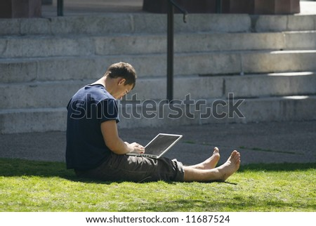 man working on laptop computer outdoors - stock photo