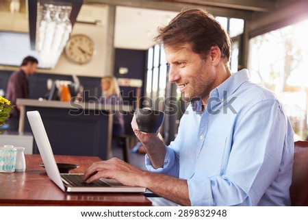 Man working on laptop in a coffee shop - stock photo