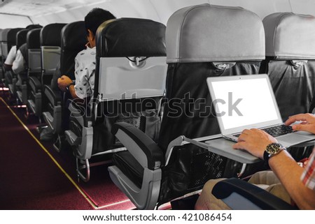 man working on laptop in aircraft cabin during his business travel