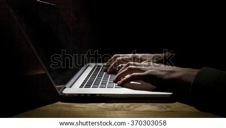 Man working on laptop in dark room - stock photo
