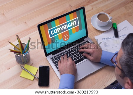 Man working on laptop with COPYRIGHT on a screen - stock photo