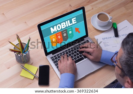 Man working on laptop with MOBILE on a screen - stock photo