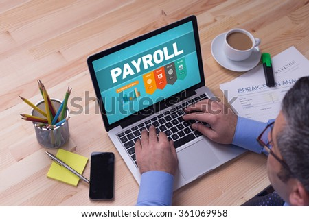 Man working on laptop with PAYROLL on a screen - stock photo