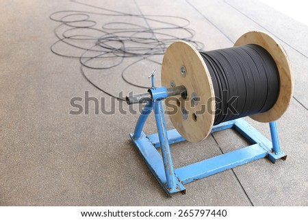 Man working on power cable drum with optical fiber cable for telecommunication and internet broadband connection - stock photo