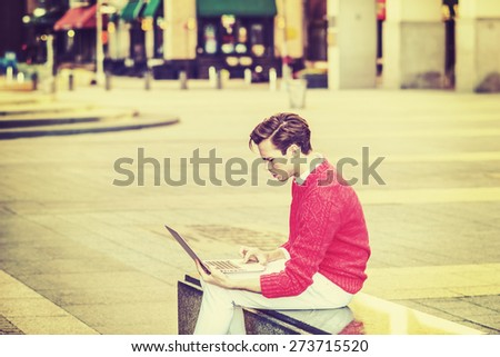 Man Working on street. Young blonde college student, wearing red sweater, white pants, sitting on marble bench, looking down, working on laptop computer. Instagram filtered effect. Modern City Life. - stock photo