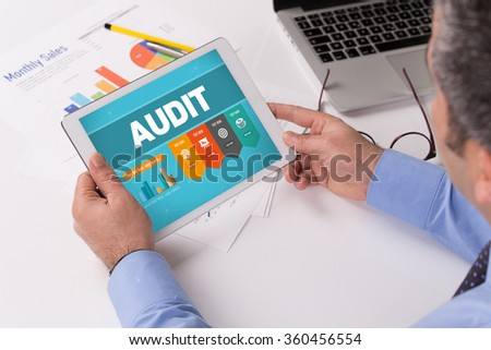 Man working on tablet with AUDIT on a screen - stock photo