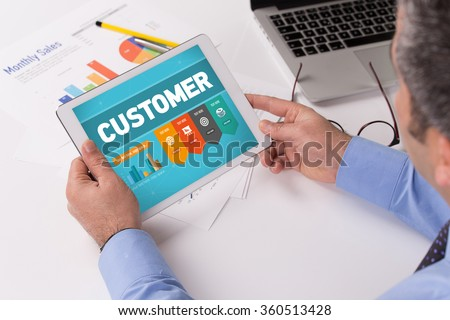 Man working on tablet with CUSTOMER on a screen - stock photo