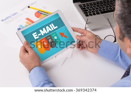 Man working on tablet with E-MAIL on a screen - stock photo