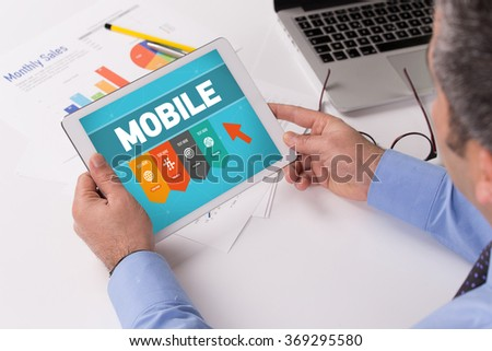 Man working on tablet with MOBILE on a screen - stock photo