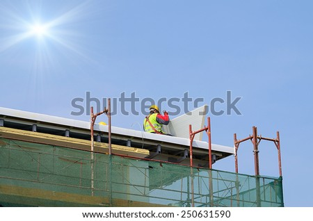 Man working on the new roof on a sunny day - stock photo