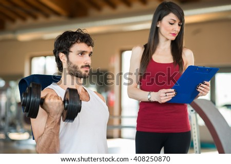 Man working out in a gym while his personal trainer looks at the execution - stock photo