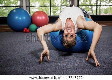 Man working out on a fitness ball at gym - stock photo