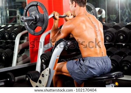 man working out with barbell in gym - stock photo