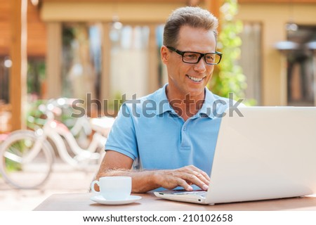 Man working outdoors. Cheerful mature man working at laptop and smiling while sitting at the table outdoors with house in the background  - stock photo