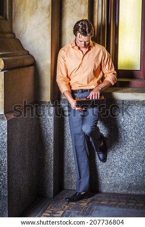 Man Working Outside. Dressing in a light orange patterned shirt, gray pants, leather shoes, a young guy is standing by an old fashion window in the corner, looking down, working on a laptop computer. - stock photo