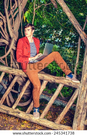 Man working outside. Wearing a dark reddish brown jacket, brown corduroy pants, a young college student sitting on wooden fence with rattan trees, working on laptop computer, looking around. - stock photo