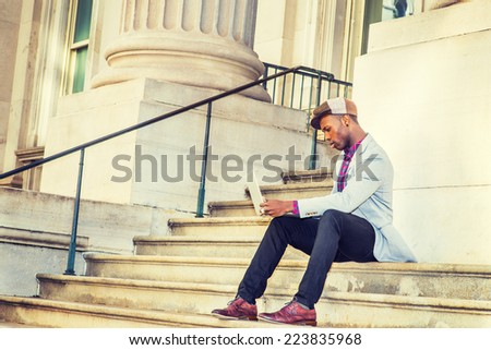 Man Working Outside. Wearing a Newsboy cap, dressing in light gray blazer, black pants, brown leather shoes, a young guy is sitting on stairs outside office building, working on laptop computer. - stock photo