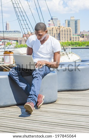 Man Working Outside. Wearing a white V neck T shirt, blue pants, brown boot shoes, a young black guy is sitting on deck, working on a laptop computer. The background is a harbor.  - stock photo