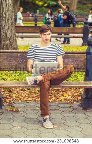Man Working Outside. Wearing striped T shirt, brown corduroy pants, sneakers, a young handsome guy is sitting on bench on a park, crossing legs, looking away, thinking, working on laptop computer. - stock photo
