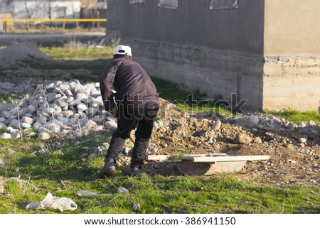 man working with a shovel. Loads of gravel for the foundation