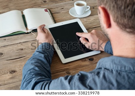 Man working with a tablet computer at a wooden table. The man clicks on the tablet screen closeup. Copy space. Free space for text