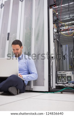 Man working with his laptop on the floor beside servers in data center - stock photo