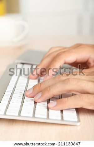 Man working with keyboard on wooden table closeup