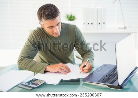 Man working with laptop and writing in his office