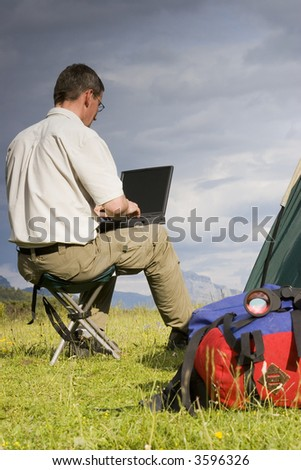Man working with laptop beside his tent in the mountains