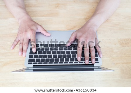 man working with laptop, man's hands on notebook computer, business person at workplace - stock photo
