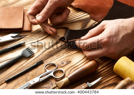 Man working with leather using crafting DIY tools