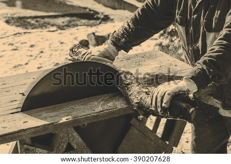 Man working with old handmade circular saw blade - stock photo