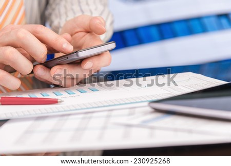 Man working with papers, charts, and smartphone in office - stock photo