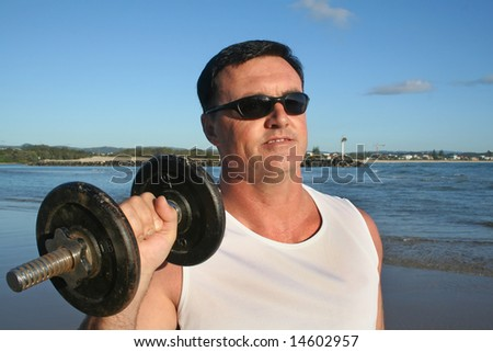 Man works out with weights on the beach just after sunrise.