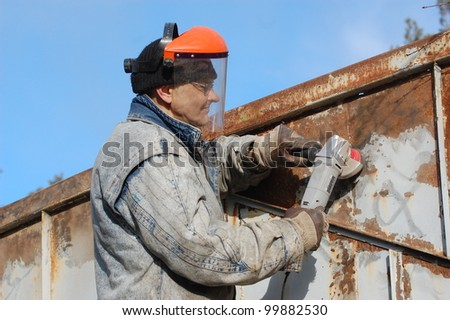 Man works with angular electric grinder. Ukraine - stock photo