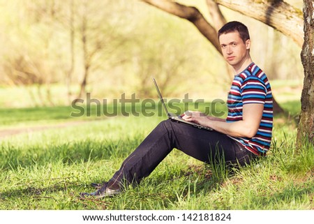 man works with laptop in sunny day in park - stock photo