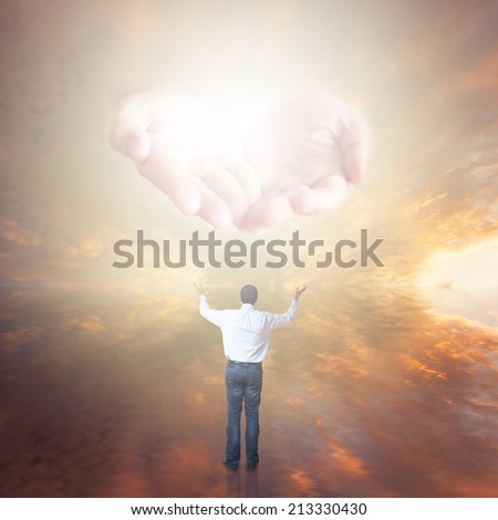 Man worshiping. The Hands of God with light coming from the sunset sky - stock photo