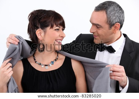 Man wrapping a shawl around his date - stock photo