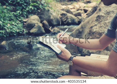 Man write notebook sitting at waterfall,vintage tone. - stock photo