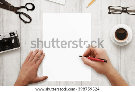 Man write with red pen on isolated, white paper. Coffee, glasses, camera, notepad, pencil on wooden table. Top view.