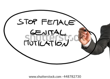 Man writing a large ringed oval sign - Stop Female Genital Mutilation - with a black marker pen on a white background, close up of his hand and the sign.