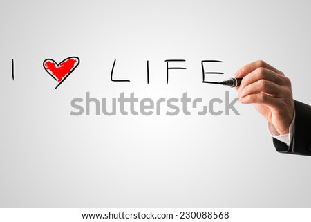 Man writing a message I love life with a red heart on a virtual interface over grey in a motivational message. - stock photo
