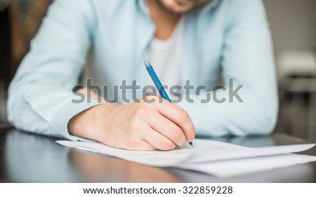 Man writing at the desk - stock photo