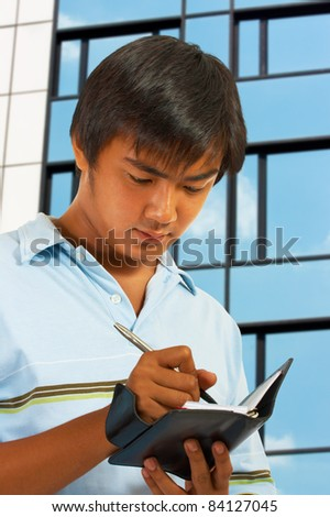 Man Writing In His Organizer Outside An Office Building - stock photo