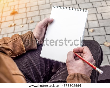 Man writing in notebook mockup - stock photo