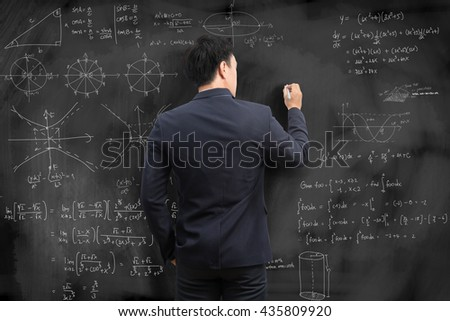 Man writing math formulas on a blackboard