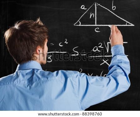 Man writing math formulas on a blackboard - stock photo